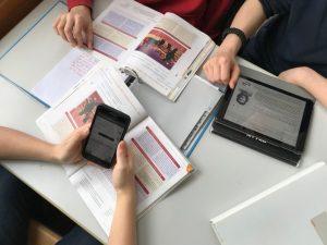 iPad, Smartphone, Buch und Heft im Unterricht